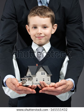 Close up of little boy and somebody's hands keeping house model. Concept of real estate and business - stock photo