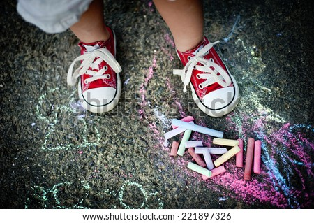 Close up of little boy in canvas shoes drawing with chalks on the sidewalk - stock photo