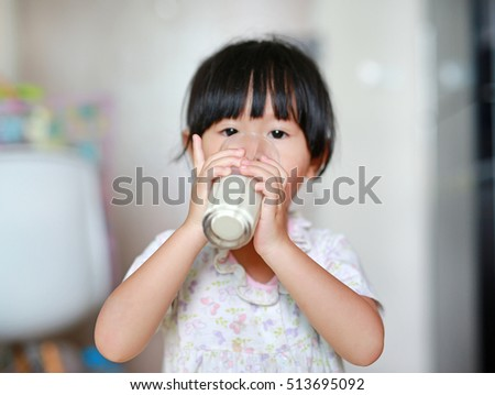 Close up of little girl drinking milk from glass indoors, Focus at hands.