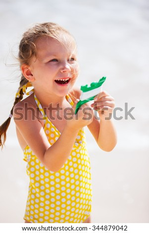 Close up of little girl flying a kite at beach