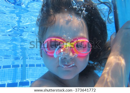 Close-up of little girl looking at camera underwater - stock photo