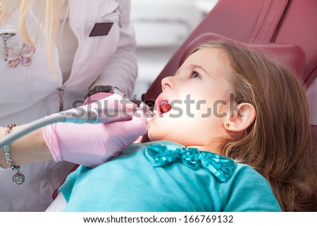 Close-up of little girl opening his mouth wide during inspection  - stock photo