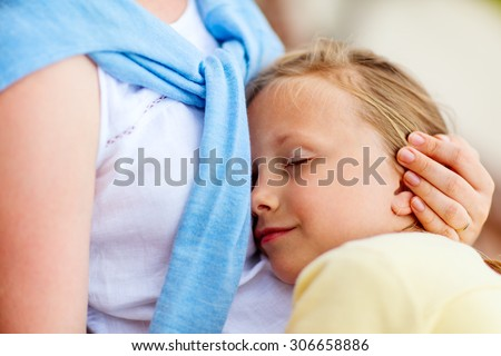 Close up of little girl sleeping on mother lap - stock photo