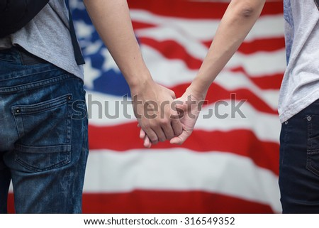 Close up of love couple holding hands together over blur crumpled fabric textures of American flag.traveler concept ,independence day concept. patriotic concept. citizenship day .selective focused - stock photo
