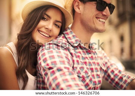 Close up of loving couple riding on bike in the city - stock photo