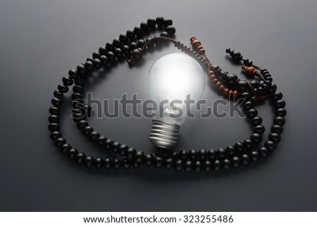 close up of low-light wood shape tasbih and bulb. Wooden rosary on grey background - stock photo