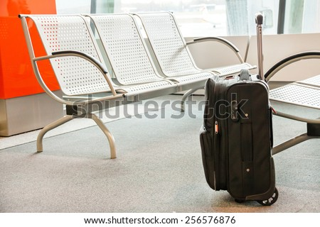 Close up of luggage (suitcase, baggage) near chairs at the airport. Indoor. Travel (vacation), business concept. Copy space. Place for your text (message). - stock photo