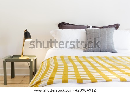 Close up of luxury bed and bedside table with lamp in designer home - stock photo