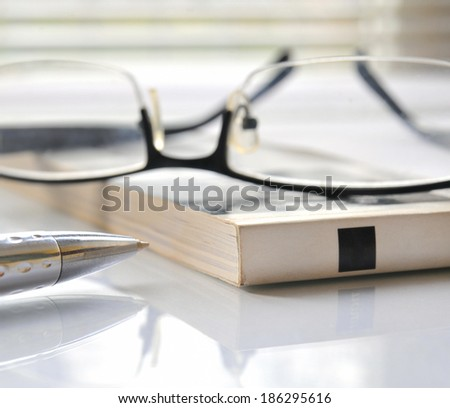Close up of magazine with glasses and ballpoint pen - stock photo