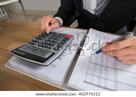 Close-up Of Male Accountant Calculating Tax At Desk In Office - stock photo