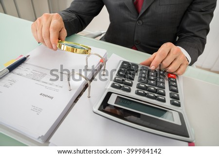Close-up Of Male Accountant Using Calculator While Holding Magnifying Glass To Analyze Bills - stock photo