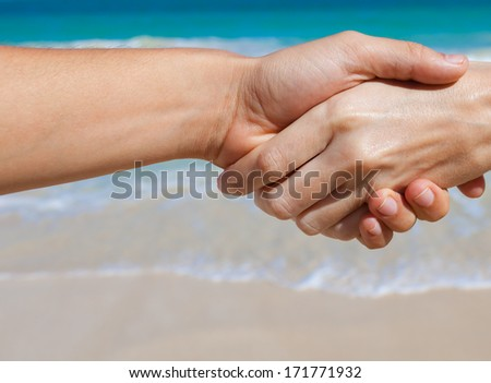Close up of male and female holding hands