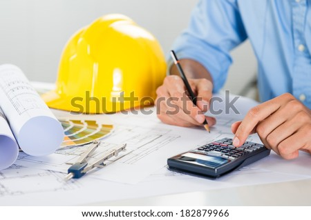 Close Up Of Male Architect Drawing On Blueprint And Using Calculator - stock photo