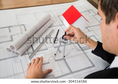 Close-up Of Male Architect Using Compass On Blueprint Paper - stock photo