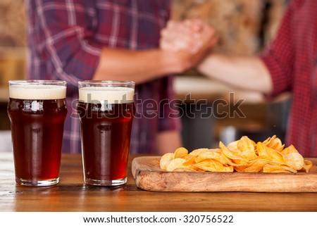 Close up of male arms shaking hands. The men are standing in bar. There are two glasses of beer and snack on the table. Focus on drink - stock photo