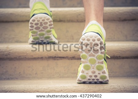 Close up of male athlete feet with sneakers running up the stairs. Rear side view. Sport, fitness, jogging, workout and healthy lifestyle concepts. - stock photo