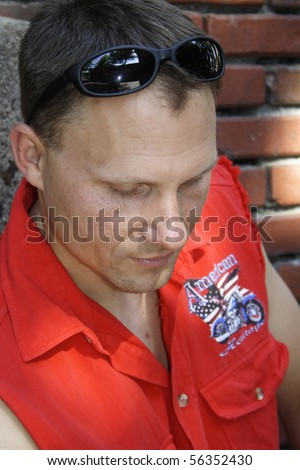Close up of male biker looking down with sunglasses on head. - stock photo