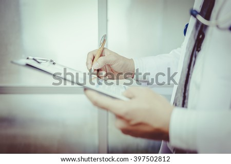 Close-up Of Male Doctor Filling The Medical Form , vintage tone - stock photo