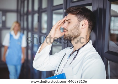 Close-up of male doctor suffering from headache while standing at hospital - stock photo