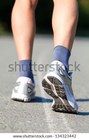 Close-up of male feet in sneakers running outdoors - stock photo