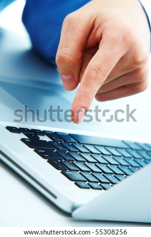 Close-up of male forefinger over keyboard of laptop during computer work - stock photo