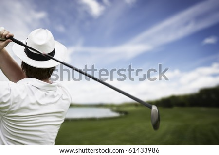 Close-up of male golf player with hat teeing-off at beautiful golf course. - stock photo