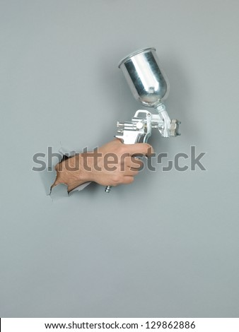 close-up of male hand holding a silver spray gun through a torn grey paper - stock photo