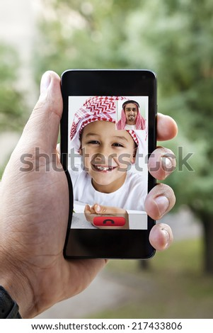 Close Up Of Male Hand Holding A Smart Phone During A Video Call With His Son - stock photo