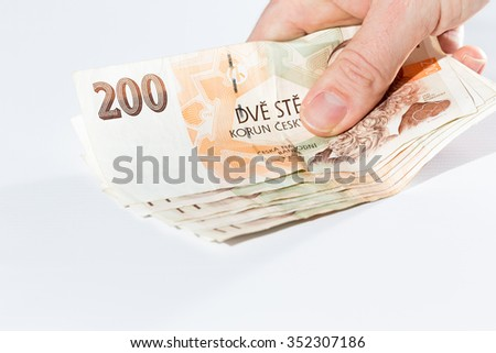 Close up of male hand holding czech banknotes isolated on white background