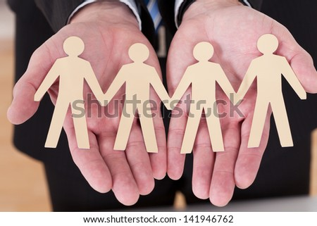 Close-up Of Male Hand Holding Human Figure Cutout