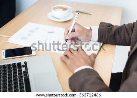 Close-up of male hand making notes in office.