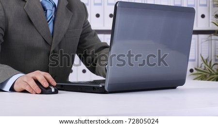 Close-up of male hand on mouse while working on laptop