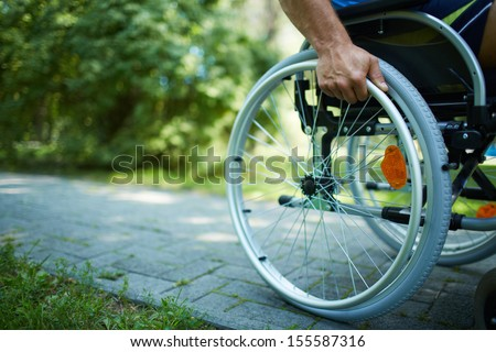 Close-up of male hand on wheel of wheelchair during walk in park - stock photo