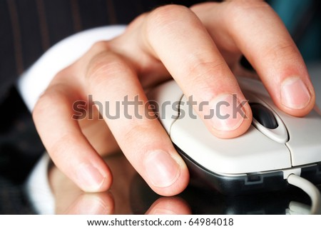 Close-up of male hand on white mouse with its reflection beneath - stock photo