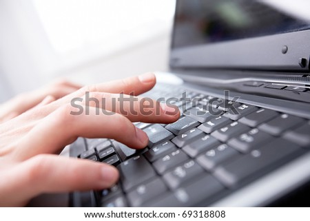 Close-up of male hand over black keyboard of laptop during typing - stock photo