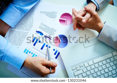 Close-up of male hand pointing at business document during discussion - stock photo
