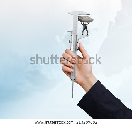 Close up of male hand pressing miniature of businessman - stock photo