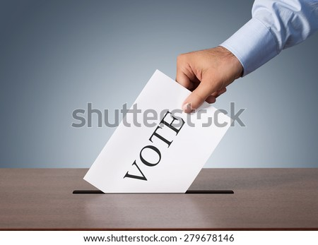 Close up of male hand putting vote into a ballot box - stock photo