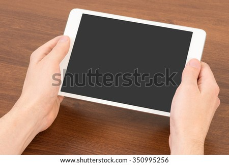 Close-up of male hand, using digital tablet. - stock photo
