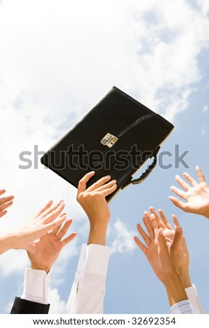Close-up of male hand with briefcase surrounded by other people hands