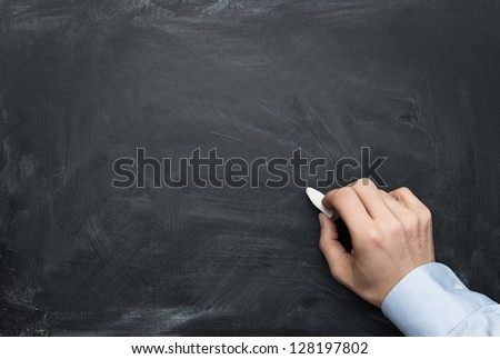 Close up of male hand writing on a blackboard with copy space for some text - stock photo