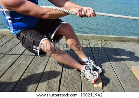 Close up of male hands and body pulling a rope in a tug of war game. - stock photo