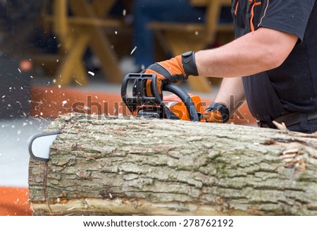 Close up of male hands cutting trunk with chainsaw - stock photo
