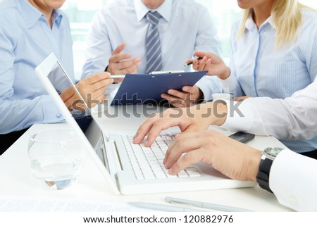 Close-up of male hands during work on the laptop, his colleagues holding a discussion in the background