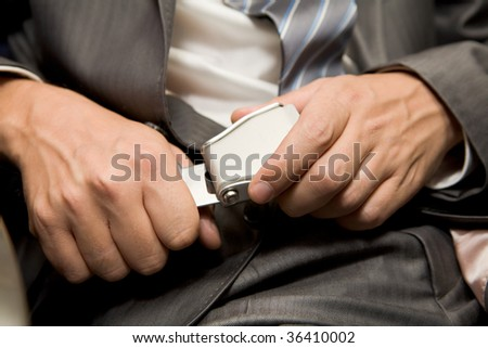 Close-up of male hands fastening security belt - stock photo