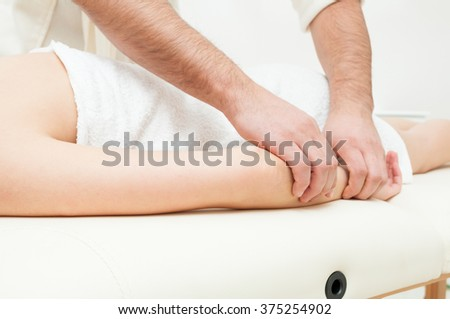 Close-up of male hands getting a woman forearm massage in the spa center - stock photo