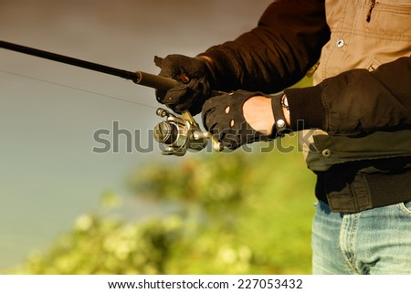 Close up of male hands in gloves holding fishing rod - stock photo