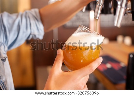 Close up of male hands of barman. He is holding a glass and taping beer into it carefully. The man is standing in bar - stock photo