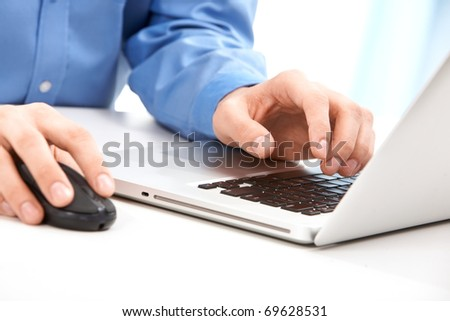 Close-up of male hands on mouse and over black keyboard of laptop during typing - stock photo