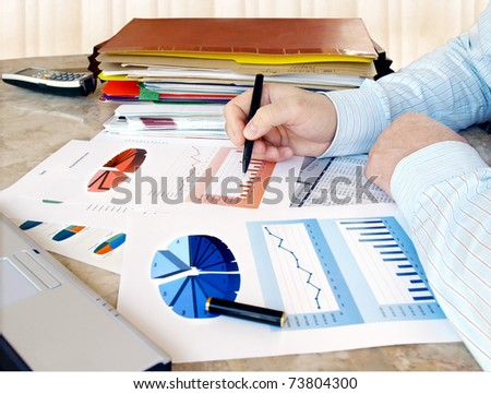 Close-up of male hands over financial  charts in the office.